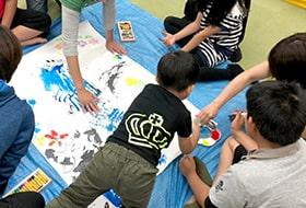 絵の具を手に塗って大きい紙にお絵かきしている画像